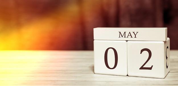 Conceito de evento de lembrete de calendário. cubos de madeira com números e mês em 2 de maio