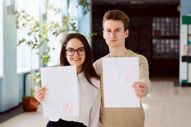 Conceito de exame, teste final. dois alunos receberam resultado do teste. a aluna obteve notas excelentes, enquanto a aluna obteve nota baixa. Foto Premium
