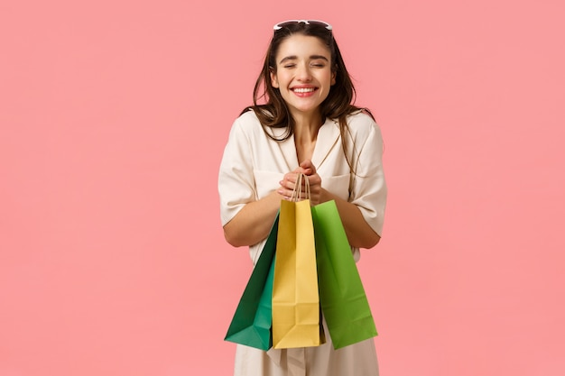 Conceito de excitação, consumo e lojas. noiva alegre e divertida, compras para o futuro casamento, gritando em êxtase, sorrindo alegremente segurando sacos desfrutando de comprar coisas, parede rosa de pé