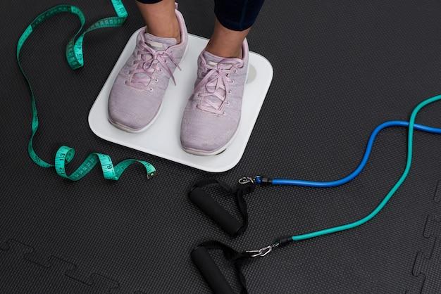 Conceito de exercício e vida saudável para perder peso. os pés da mulher em uma escala moderna.