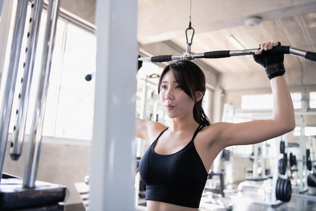 Conceito de exercício. uma linda garota está exercitando no ginásio. uma linda garota está jogando uma máquina de cabo.