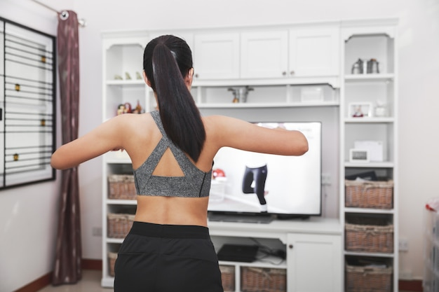 Conceito de exercícios caseiros saudáveis, mulher asiática em forma fica em casa e treinando aula de exercícios esportivos online na tv em casa, nova vida normal do surto de covid-19