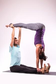 Conceito de exercícios de ioga. jovem casal saudável em posição de ioga em fundo branco