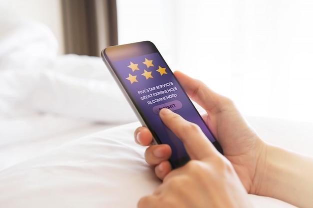 Conceito de experiência do cliente. feliz, cliente, usando, smartphone, cama