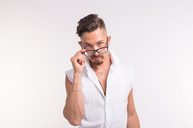 Conceito de expressão e pessoas - jovem bonito olhando para você através dos óculos em branco