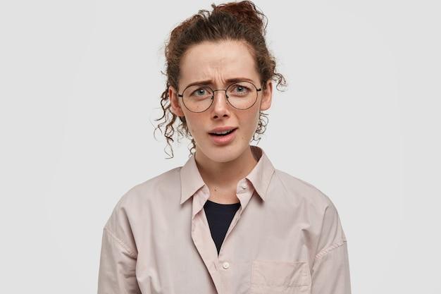 Conceito de expressões faciais negativas. mulher infeliz, indignada e sardenta de cabelos cacheados, franze a testa com desprazer, veste camisa bege gigante, ouve algo desagradável do interlocutor