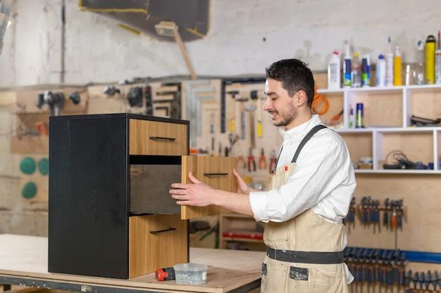 Conceito de fábrica de móveis e pequenas e médias empresas - homem coleta detalhes de móveis