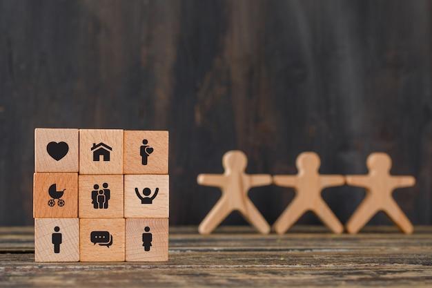 Conceito de família com ícones em cubos de madeira, figuras humanas na vista lateral da mesa de madeira.