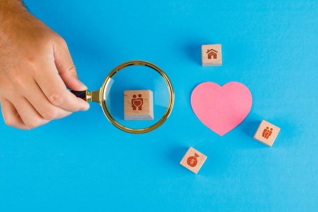 Conceito de família com papel cortado coração na mesa azul plana leigos. mão segurando a lupa sobre o cubo de madeira.