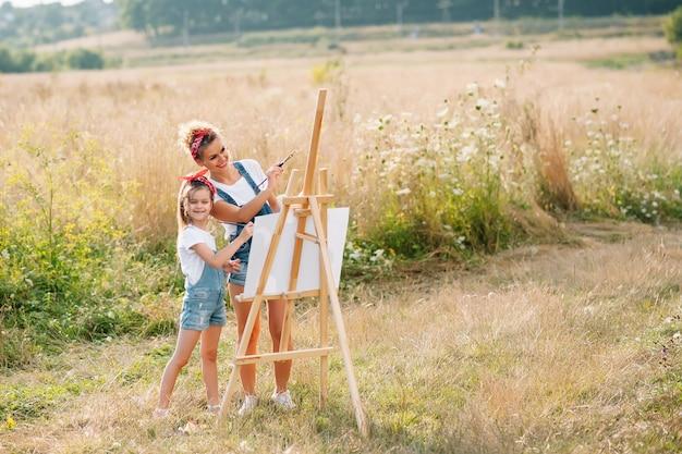 Conceito de família, crianças e pessoas - mãe e filha felizes desenhando e conversando sobre uma superfície verde