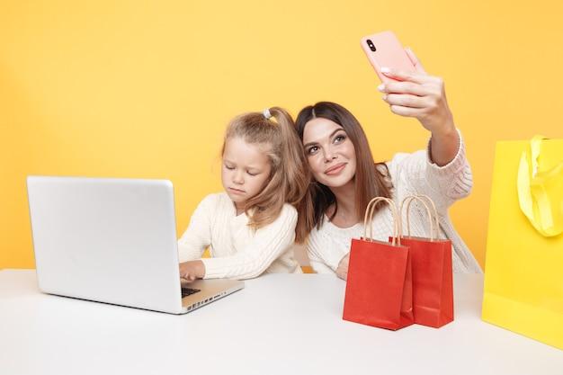 Conceito de família de blogueiros. linda mãe e linda filha fazendo foto juntos no telefone.