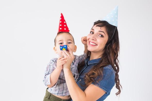 Conceito de família e férias - retrato de mãe feliz e bebê na festa de aniversário.
