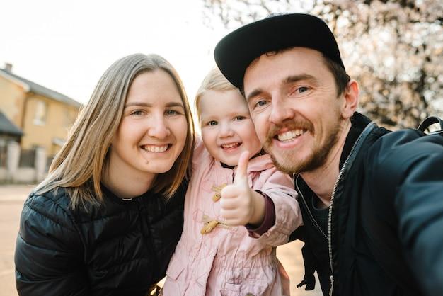 Conceito de família feliz e saudável. garoto, mãe, pai, andar na rua, tirando foto de selfie ao ar livre.