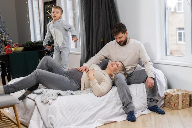 Conceito de família feliz mãe, pai e filho se divertem em casa família caucasiana dentro de casa mãe grávida, pai barba e menino engraçado deitam no sofá