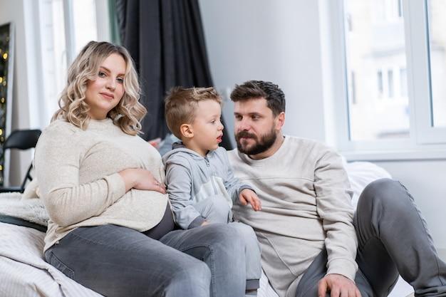 Conceito de família feliz mãe pai e filho se divertem em casa família caucasiana dentro de casa mãe grávida pai barba e menino engraçado