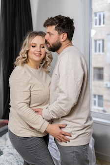 Conceito de família feliz. marido abraço esposa grávida barriga em pé sala de estar interna perto do sofá caucasiano homem e mulher gravidez e novo conceito de vida. amor e cuidado