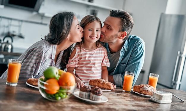 Conceito de família feliz na cozinha. mamãe e papai beijam a filha, preparando-se para um delicioso café da manhã.