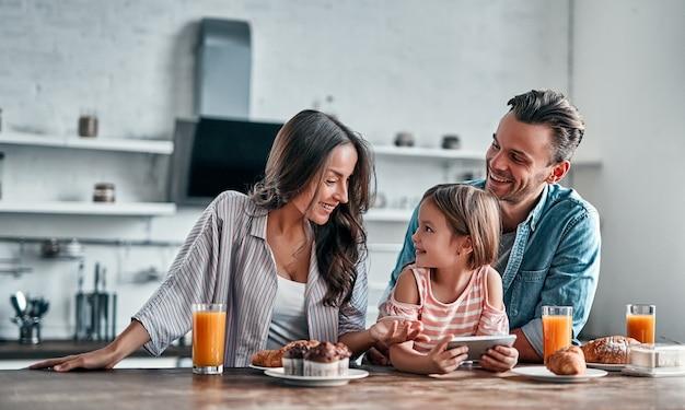 Conceito de família feliz na cozinha. menina bonitinha e seus lindos pais estão usando um telefone inteligente e sorrindo enquanto se preparam para um delicioso café da manhã.