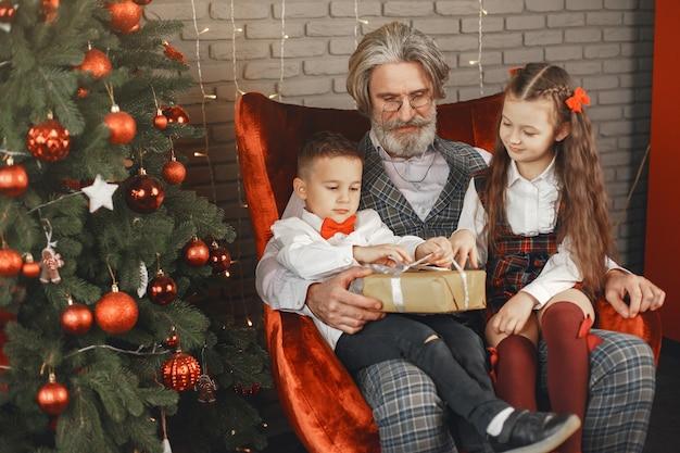 Conceito de família, feriados, geração, natal e pessoas. crianças em um quarto decorado para o natal