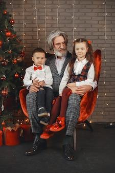 Conceito de família, feriados, geração, natal e pessoas. crianças em um quarto decorado para o natal.
