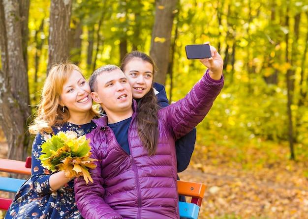 Conceito de família, infância, estação, tecnologia e pessoas - família feliz fotografando selfie no parque outono.