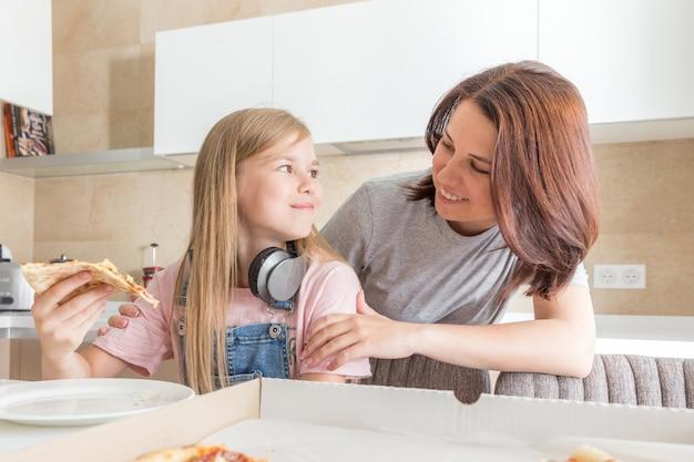 Conceito de família, mãe e filha comendo uma pizza saborosa