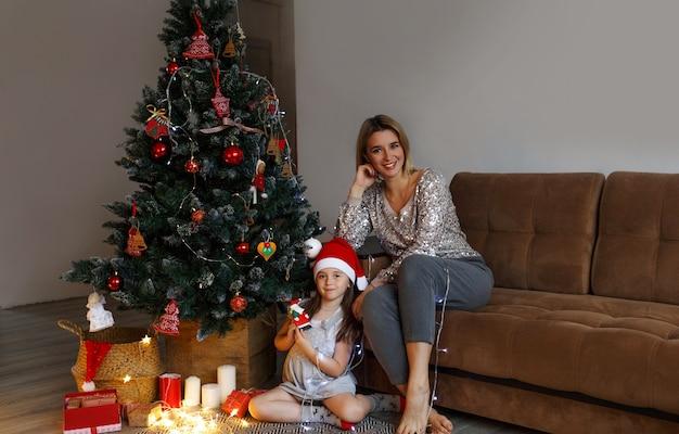 Conceito de família, natal, feriados e mãe e filha felizes sentadas em casa no sofá
