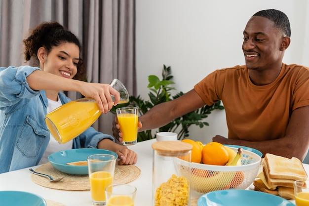 Conceito de família negra feliz com suco derramado de mulher para parceiro