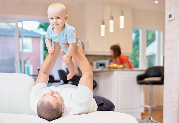 Conceito de família, pai e bebê brincando no sofá, infância feliz. tiro interno na cozinha. criança em seus braços, a criança joga no teto, família feliz