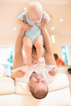 Conceito de família, pai jogando no sofá com o bebê e o irmão, infância feliz. tiro interno na cozinha. um bebê nos braços, um bebê joga no teto, família feliz