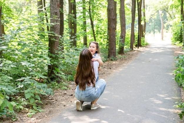 Conceito de família, paternidade e natureza - mãe com filha se divertindo no parque verde.