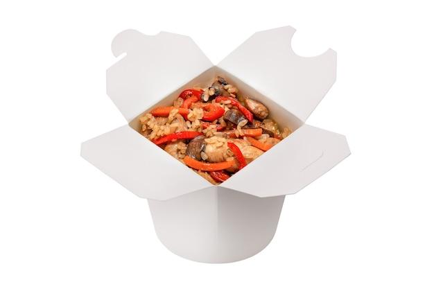 Conceito de fast food asiático caixa aberta de arroz com frango e vegetais cozidos em uma wok isolada