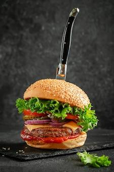 Conceito de fast food. hambúrguer com faca na placa de ardósia em fundo escuro.