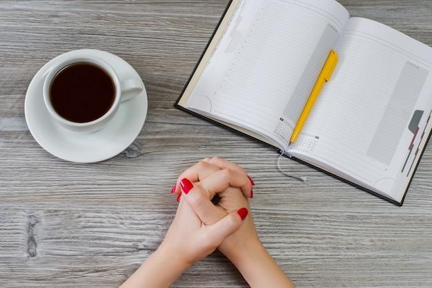 Conceito de fazer uma escolha entre educar e descansar. foto da vista superior das mãos cruzadas de uma mulher, xícara de café, bloco de notas aberto com caneta na mesa de madeira