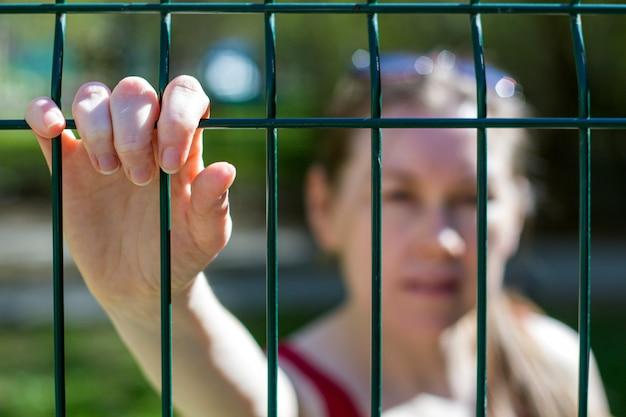 Conceito de fechamento da fronteira, isolamento. incapacidade de sair. mãos femininas na treliça como um símbolo de limitação, fronteiras, espera