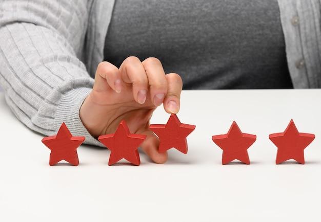 Conceito de feedback da experiência do cliente. cinco estrelas vermelhas, a melhor avaliação de excelentes serviços com uma mão feminina para atender. mesa branca