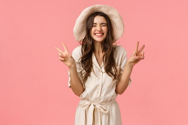Conceito de felicidade, alegria e alegria. concurso bobo, namorada feminina de chapéu e vestido, mostrando sinais de paz e rindo despreocupado, curtindo férias, estar em viagem, parede rosa