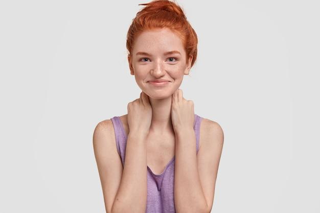 Conceito de felicidade e alegria. mulher jovem caucasiana satisfeita com coque ruivo