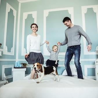 Conceito de felicidade familiar amando pais brincando com a filha bebê na cama no quarto
