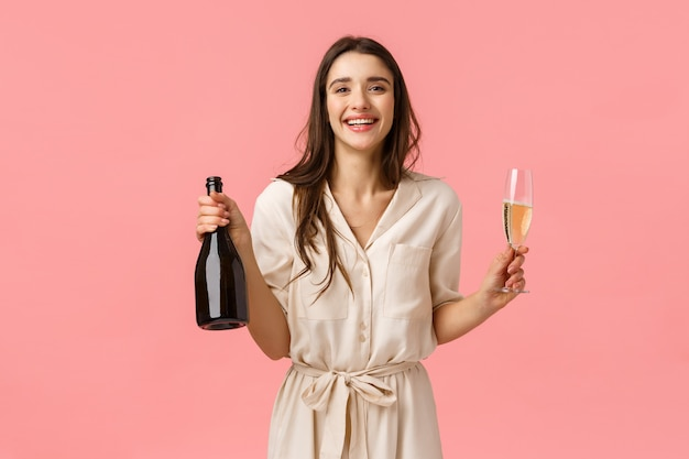 Conceito de felicidade, romance e amor. elegante lindo sorrindo, mulher feliz comemorando aniversário, dia dos namorados, segurando a garrafa de champanhe e copo, desfrutando de bebida e levante o copo para a ocasião