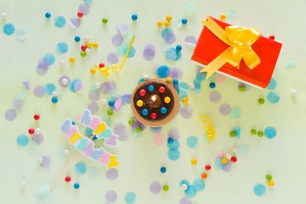 Conceito de feliz aniversário. bolo, caixa de presente, confetes e itens de festa espalhados sobre a mesa. vista do topo