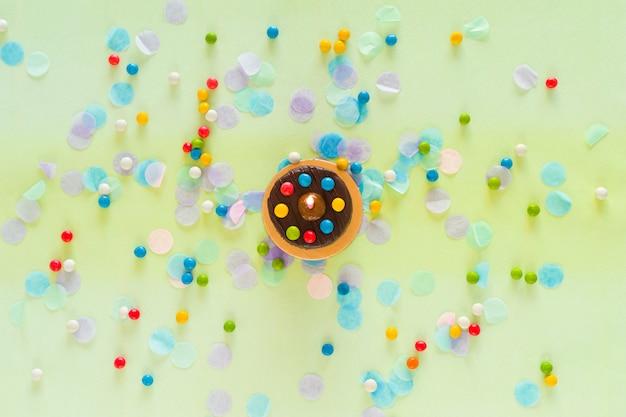Conceito de feliz aniversário. bolo, confete e itens de festa espalhados sobre a mesa. vista do topo