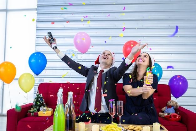 Conceito de feliz ano novo 2021. casal feliz acendendo fogos de artifício de papel com champanhe e biscoitos na mesa na festa de natal e réveillon