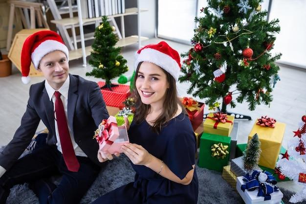 Conceito de feliz ano novo 2021. casal feliz segurando a troca de presentes e dar um presente na festa de natal e reveillon fundo de árvore de natal
