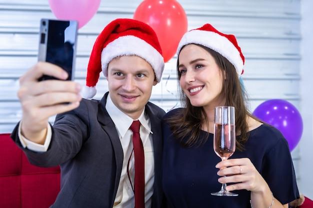 Conceito de feliz ano novo 2021. selfie de casal feliz segurando a taça de champanhe na festa de natal e ano novo