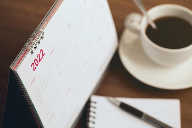 Conceito de feliz ano novo 2022 feche a programação do calendário 2022 com uma xícara de café e uma nota em branco