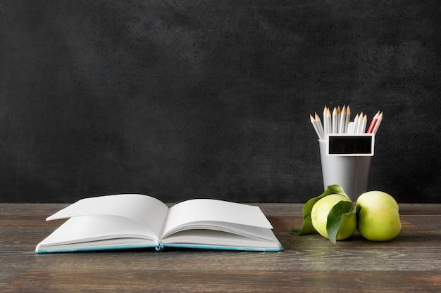 Conceito de feliz dia do professor de livro e maçãs