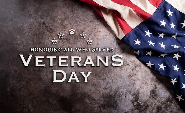 Conceito de feliz dia dos veteranos. bandeiras americanas contra um fundo de pedra escura. 11 de novembro.
