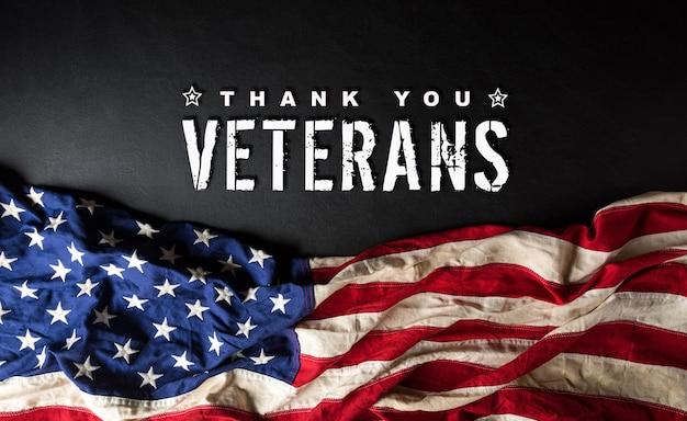Conceito de feliz dia dos veteranos. bandeiras americanas contra um quadro negro