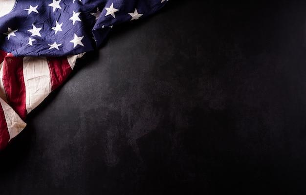 Conceito de feliz dia dos veteranos. bandeiras americanas vintage contra pedra preta
